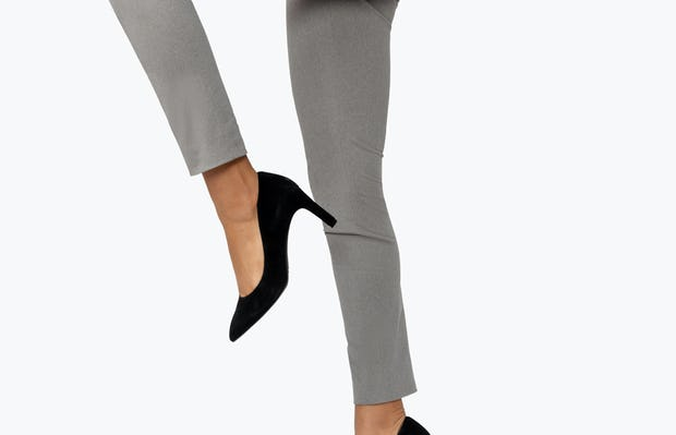 Women's Grey Heather Kinetic Skinny Pants on Model Jumping in Air with Knee Raised