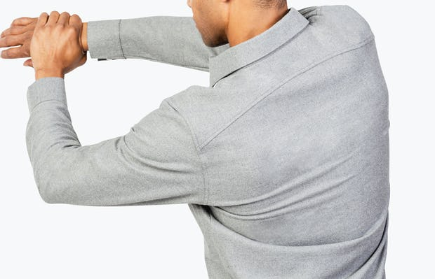 Men's Grey Fusion Overshirt model facing backward with left hand grabbing extended right arm