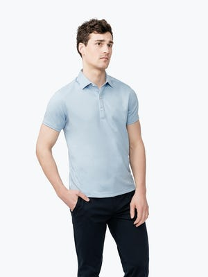 Men's Blue Heather Apollo Polo on model facing forward with hand in pant pocket
