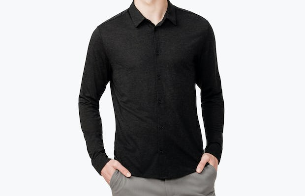 Men's Black Composite Merino shirt model facing forward with hands in pockets