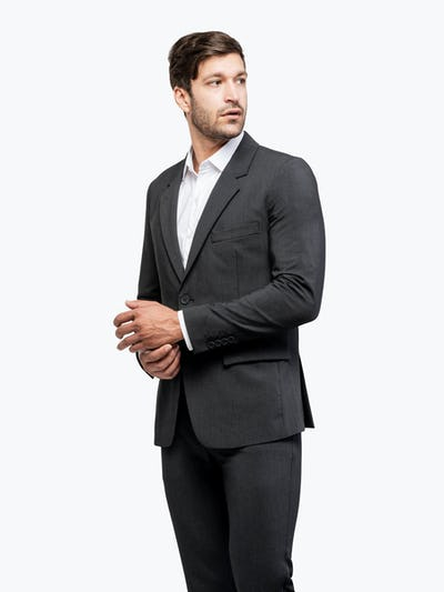 Men's Dark Charcoal Velocity Suit on Model Turned Right and Adjusting Buttons on Sleeves
