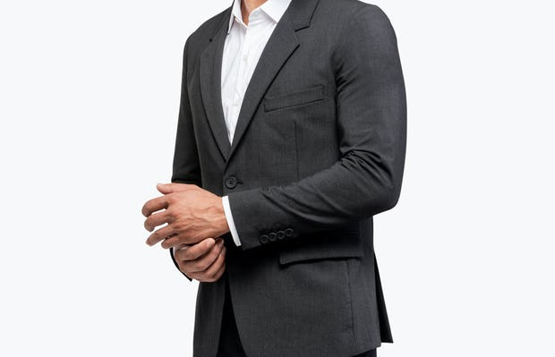 Men's Dark Charcoal Velocity Suit Jacket on Model Turned Right and Adjusting Sleeve