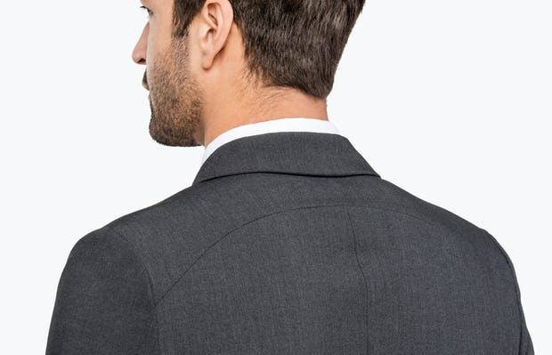 Men's Dark Charcoal Velocity Suit Jacket on Model facing Backward in Close-Up of Collar and Shoulder