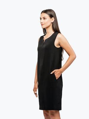 Women's Black Swift Sleeveless Dress on Model Facing Left with Hand in Her Pocket