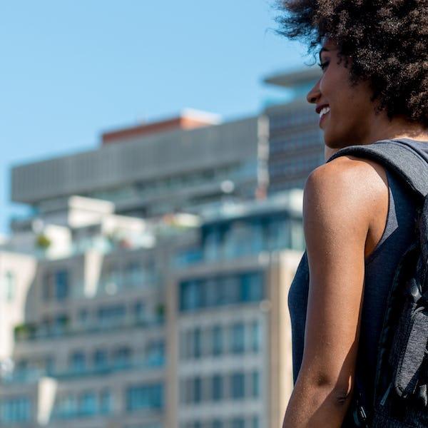 Backshot of woman wearing AER bag in a city