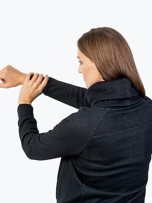 Women's Black Hybrid Fleece Funnel Neck on Model Stretching Her Arm
