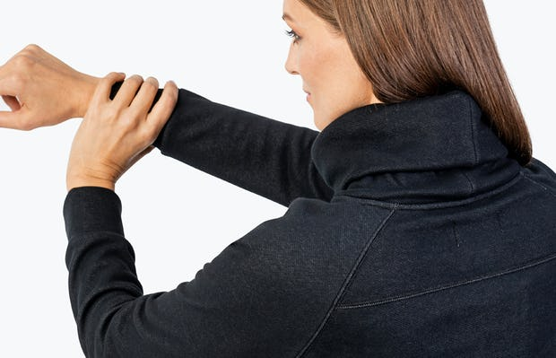 Women's Black Hybrid Fleece Funnel Neck on Model Stretching Her Arm