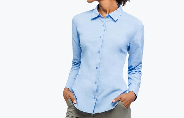 Women's Solid Blue Nylon Aero Dress Shirt on Model Looking to Her Right with Hand in Her Pockets