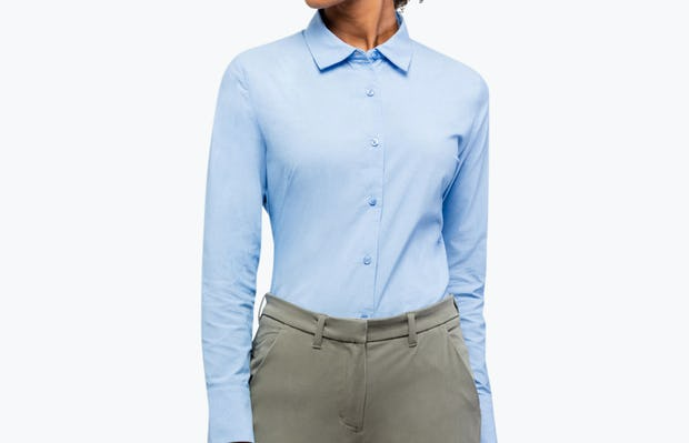 Women's Solid Blue Nylon Aero Dress Shirt on Model Looking to Her Right with Shirt Tucked In
