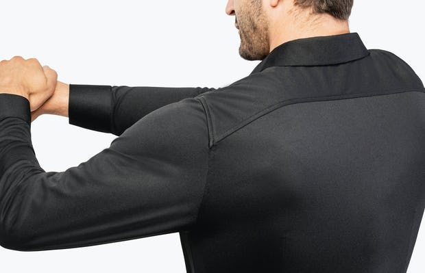 Men's Black Brushed Apollo Dress Shirt model facing backward with arms stretched and hands clasped to the left