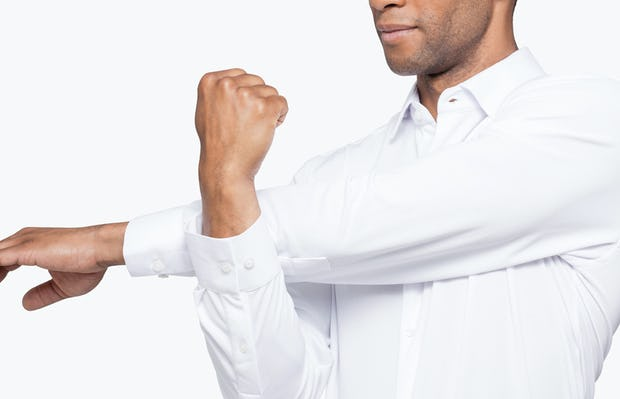 Men's White Apollo Dress Shirt model facing forward and to the left stretching left arm