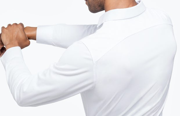 Men's White Apollo Dress Shirt model facing backward with arms stretched and hands clasped to the left