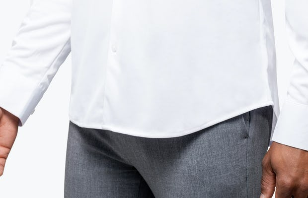 Men's White Apollo Dress Shirt model facing forward and to the right with closeup of untucked shirt