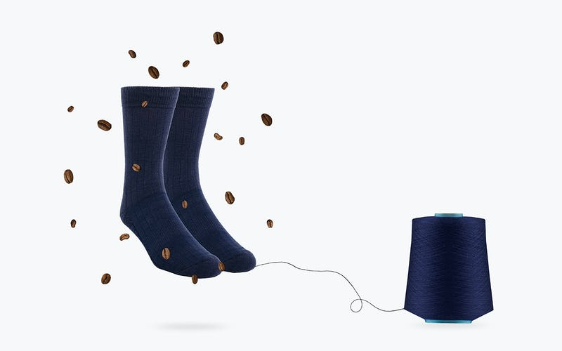 Socks Connected to a Roll of Yarn and Surrounded by Coffee Beans