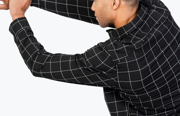 Men's Black Fusion Overshirt model facing backward with left hand grabbing extended right arm