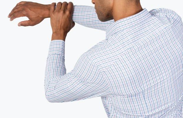 Men's Lavender Tattersall Aero Zero Dress shirt model facing backward with left hand grabbing extended right arm