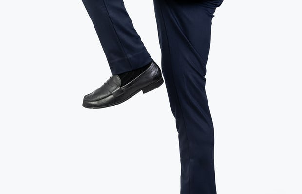Men's Navy Fusion Pant model facing to their right and jumping