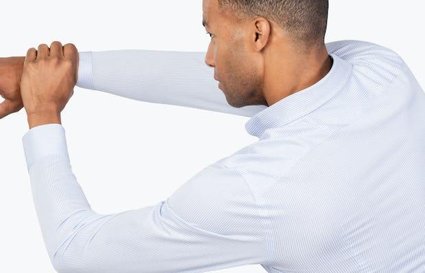 Men's Blue Stripe Gemini Kit shirt model facing backward with left hand grabbing extended right arm
