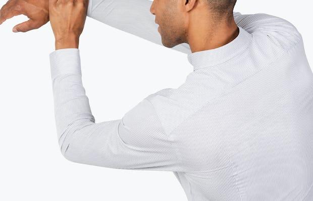 Men's Grey Stripe Gemini Knit shirt model facing backward with left hand grabbing extended right arm