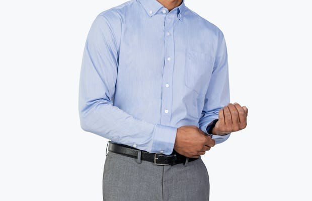 Men's Blue Gemini Woven shirt model facing forward and adjusting left cuff