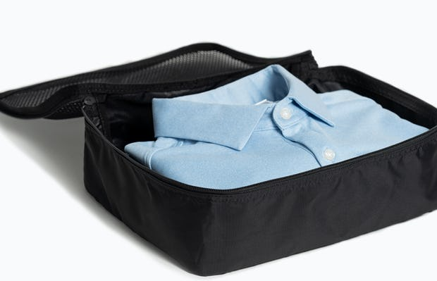 Black Aer packing cube open with folded clothes inside