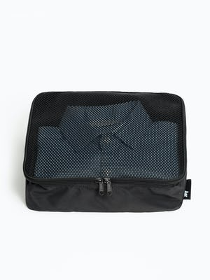 Black Aer packing cube with mesh top zipped with folded clothes inside