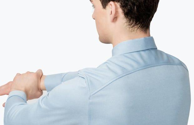 Men's Blue Heather Apollo Dress Shirt on Model Facing Backward Stretching Arms Forward
