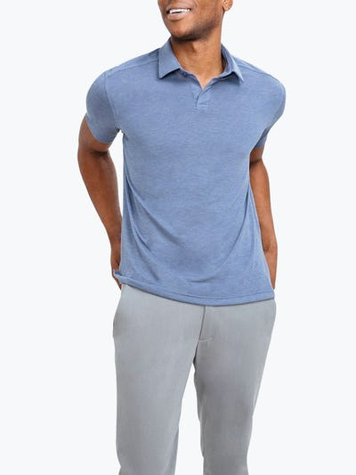Men's Blue Composite Polo on Model Facing Forward with Hands in Pants Pockets