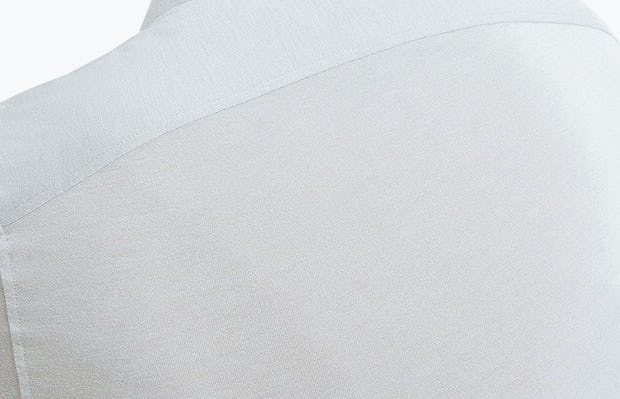 Men's Grey Composite Polo on Model Facing Backward in Close-Up of Model Stretching