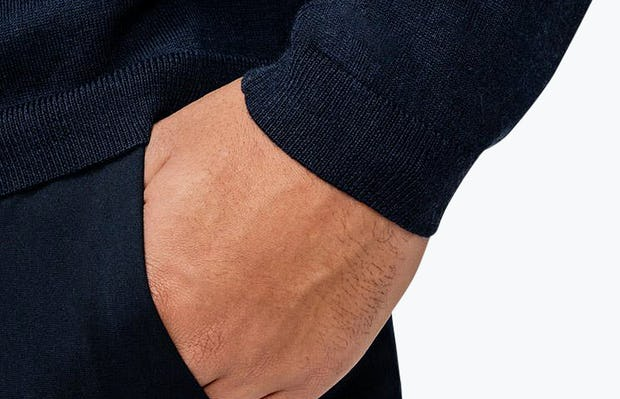 Men's Navy Atlas V-Neck Sweater on Model Facing Side in Close-Up of Sleeve Cuff