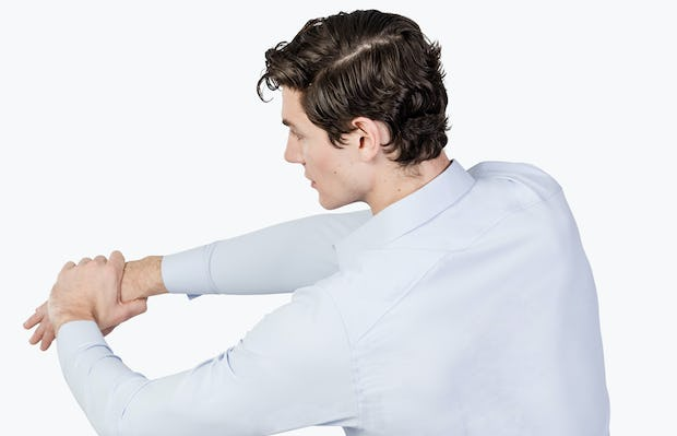Men's Blue Aero Zero Dress shirt model facing backward with left hand grabbing extended right arm