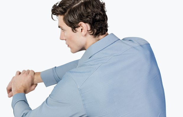 Men's Sky Blue Oxford Brushed Apollo Dress Shirt model facing backward with arms stretched and hands clasped to the left