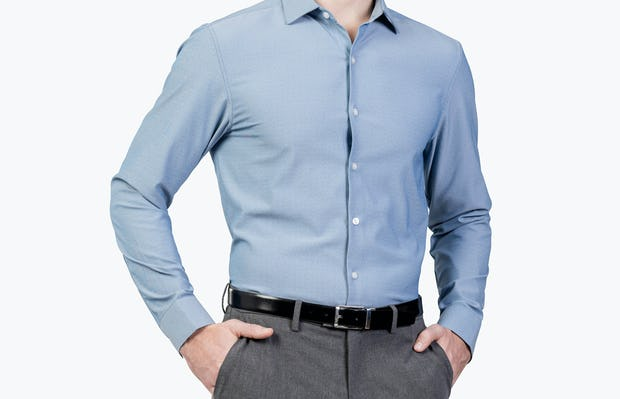Men's Blue Oxford Aero Zero Dress shirt model facing forward and to the left with hands in pockets