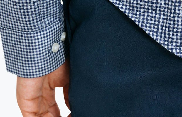Men's Navy Gingham Hybrid Button Down on Model Facing Backward in Close-Up of Bottom Hem Line and Sleeve Cuff