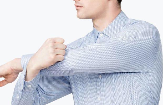 Men's Aero Dress Shirt - Blue on Blue Grid model facing forward doing an arm stretch