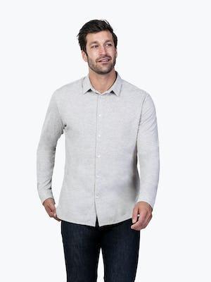 Men's Grey Composite Merino shirt model facing forward with hand on bottom of shirt