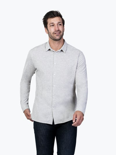 Men's Grey Composite Merino shirt model facing forward with hand on bottom of shirt