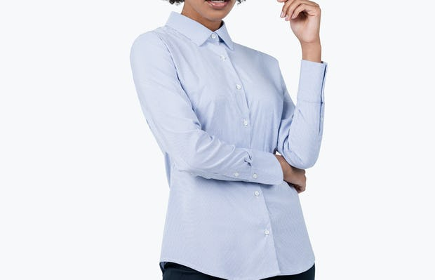 Women's Blue Stripe Aero Dress Shirt on Model with Right Arm Tucked Under Her Left Elbow