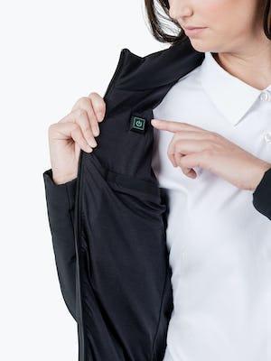 Women's Black Mercury Intelligent Heated Jacket on Model Pressing Jacket Power Button