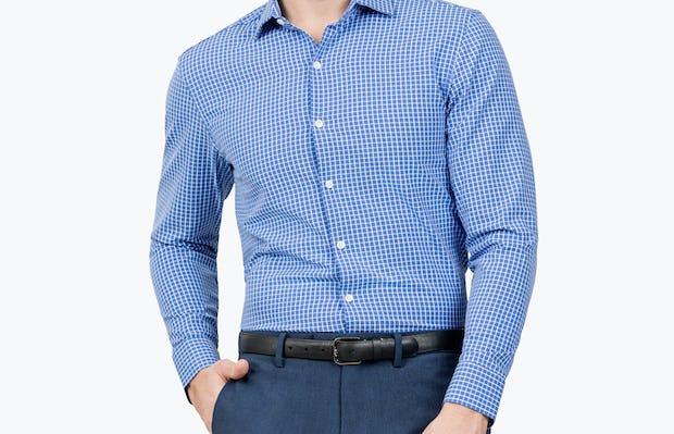 Men's Blue Grid Aero Zero Dress shirt model facing forward with hand in pocket