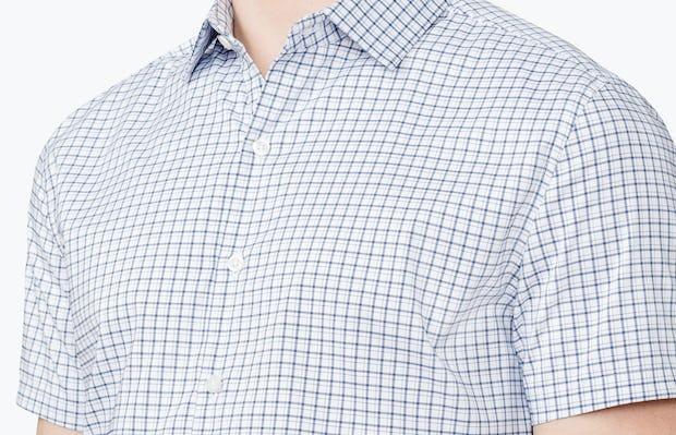 Men's Navy Plaid Aero Short Sleeve Dress Shirt on Model Facing Forward in Close-Up of Unbuttoned Collar