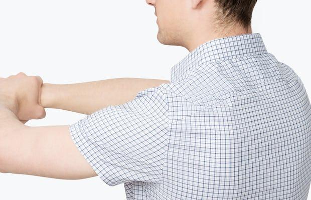 Men's Navy Plaid Aero Short Sleeve Dress Shirt on Model Facing Backward Stretching Arms Forward
