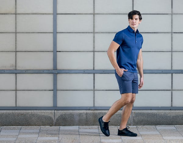 Man standing against wall while wearing Navy Kinetic Shorts and Apollo Polo