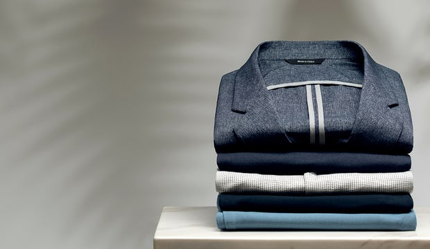 Stack of folded shirts with Kinetic Dot Air Blazer on top