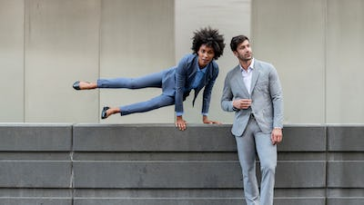 Woman jumping over wall wearing Indigo Heather Kinetic Suit next to man standing against wall wearing Grey Heather Kinetic Suit