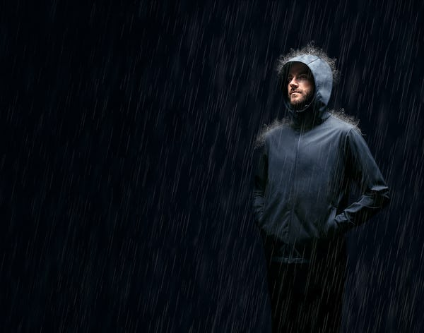 Man standing in rain wearing Doppler Jacket