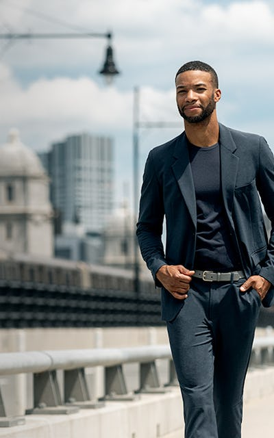 Man wearing blazer walking across a bridge