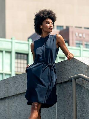 Women's Hybrid Seersucker Dress Navy model outdoors with hand in pocket leaning on railing