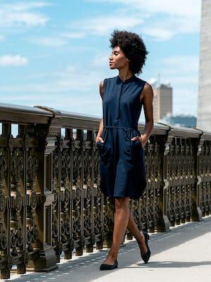 Women's Hybrid Seersucker Dress Navy model outdoors with hands in pockets walking on bridge