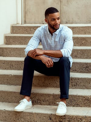Men's Aero Button Down in Grey Blue Plaid model sitting on steps outdoors